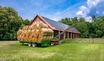 Green trailer filled with hay bales parked in the front of brick barn on a farm. Solar panels installed on the roof of the barn.